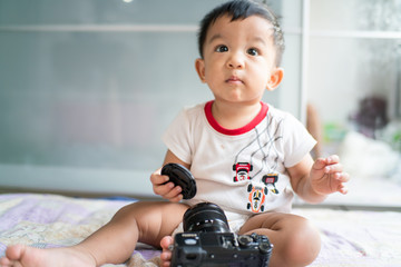 Adorable baby boy playing with camera