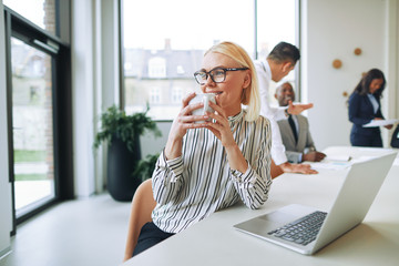 Smiling businesswoman drinking a coffee while working in an office