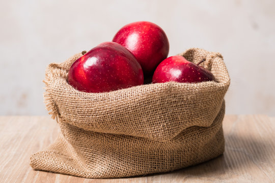 Bag with apples. Studio image. Red apples in a burlap bag on a wooden background. Fabric bag full of apples.
