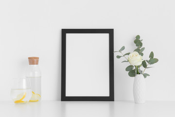 Black frame mockup with a rose and eucalyptus in a vase, glass and a bottle on a white table. Portrait orientation.