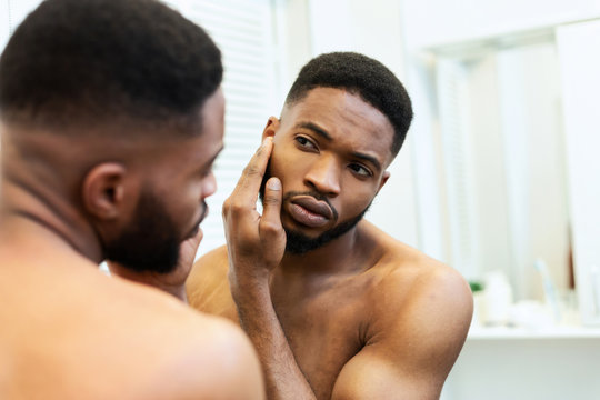Young african american guy checking his face skin in mirror