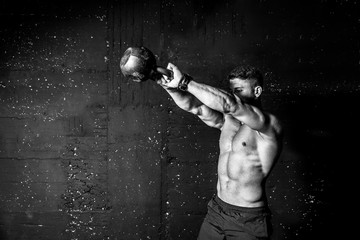 Young strong sweaty focused fit muscular man with big muscles holding heavy kettle bell for swing...