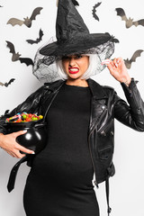 Foto op Aluminium Art Studio pregnant and angry woman in witch hat and wig holding pot with candies in Halloween