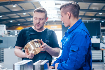 Master discussing a workpiece with his apprentice or trainee