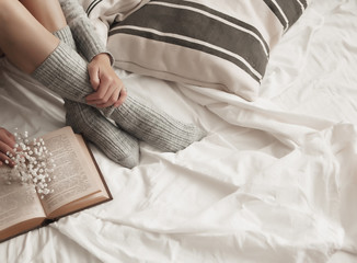 at home on the bed a girl in knitted socks is reading a book