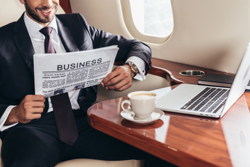cropped view of smiling businessman in suit reading business newspaper in private plane