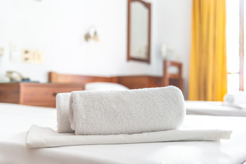 Two white towels are on the bed in hotel room. Close-up horizontal background. Space for text.