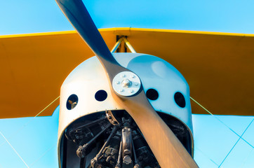 propeller with a motor and yellow wings of a vintage airplane