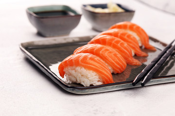 Photo sur Aluminium Sushi bar close up of sashimi sushi set with chopsticks and soy - sushi roll with salmon and sushi roll with smoked eel