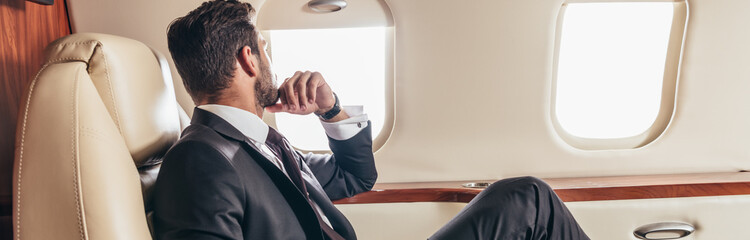 panoramic shot of businessman in suit looking through window in private plane