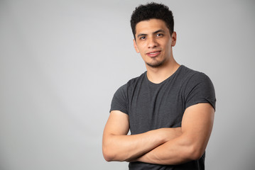 Young Hispanic man with arms crossed smiling, brunette man in studio looking at camera