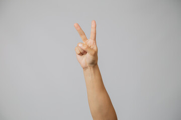 Man's hand with number two, hand raising two fingers index up in studio with gray background, symbol of love and peace
