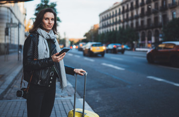 Traveler woman with suitcase calling mobile phone waiting yellow auto taxi in evening street europe city Barcelona. Girl tourist using smartphone technology internet online gadget cellphone