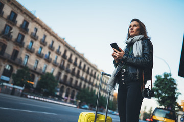 Traveler woman with suitcase calling mobile phone waiting yellow taxi in evening street europe city...