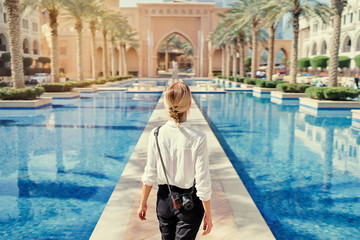 Enjoying travel in United Arabian Emirates. Young woman with camera walking on Dubai Downtown.