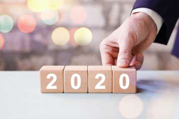 Businessman hand arranging wood block with new year 2020 on bokeh background.