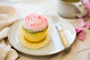 vanilla cupcake with pink frosting on plate