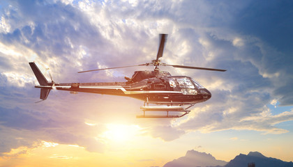 Foto op Plexiglas Helicopter Fying helicopter in the setting sun