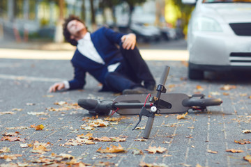 Accident with an electric scooter. A man fell from a scooter on a city street.