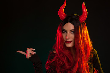 Image of Halloween makeup look of beautiful demon on dark background with copyspace. Beautiful Model with red hear wearing a headpiece with red horns