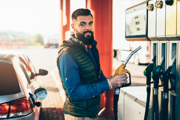 Young handsome adult man standing on gas station and fueling his car.