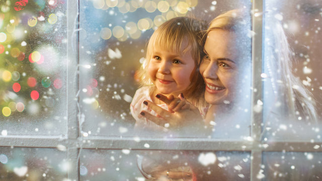 On Christmas Eve Mother and Daughter Looking Through Window with Snowy Effect. Garland Shines Bright on a Window.