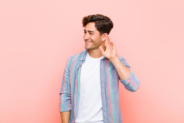 young handsome man smiling, looking curiously to the side, trying to listen to gossip or overhearing a secret against pink background
