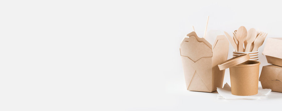 Eco kraft paper tableware. Paper cups, dishes, fast food containers and wooden cutlery on white background. Recycling and plastic free concept.