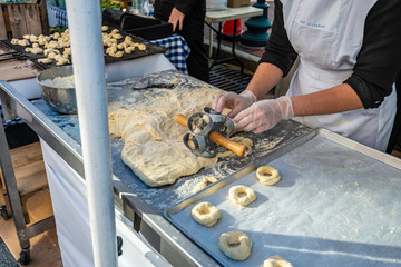 Amish women making fresh doughnuts by hand at outdoor market
