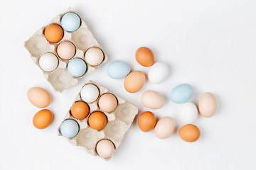 Natural Colored brown and white Eggs in egg box. Compositions in pastel colors. Easter consept.  Flat lay, top view