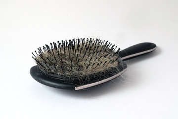 Black hair brush with hair in the bristles