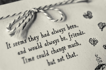 Monochrome low-key image of note card with a ribbon bow and a quote on friendship