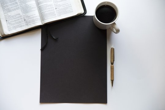 Overhead shot of a black rectangle on a white surface near a Bible, coffee and a pen