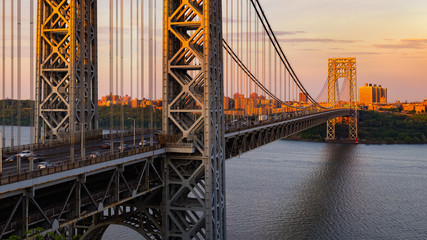 The George Washington Bridge (long-span suspension bridge) across the Hudson River at sunset. Uptown and Fort Washington Park, New York City, USA
