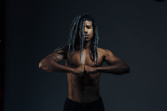 Portrait of a shirtless young man with arms together in studio
