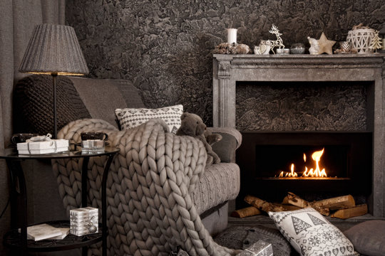 Modern cozy interior in gray shades with an armchair in front of fireplace. On the chair there are nice knitted blanket, cushions and Teddy bear. A lamp and gifts on the table.