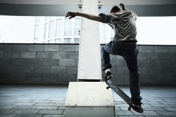 Young Caucasian man jumping on a skateboard on the street.