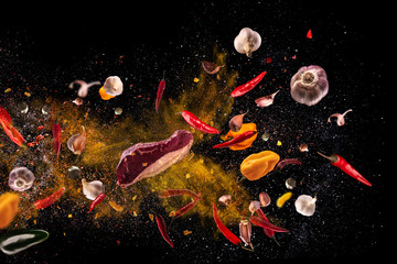 Hot red pepper, garlic, different spices powder meat stakes flying on a black background Motion freeze photo composition