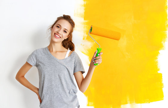 Repair in apartment. Happy young woman paints wall