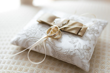 Golden wedding rings lies on a small decorated pillow