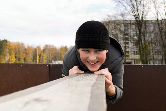 A boy in warm clothes overcomes an obstacle course lying on a wooden bar. Outdoor sports training in cold weather.