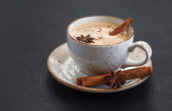 Indian Masala chai tea. Traditional Indian hot drink with milk and spices on dark stone background closeup.