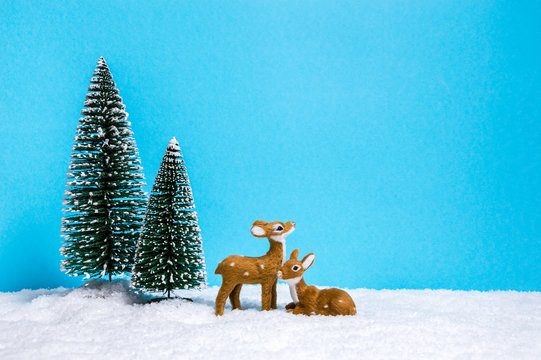 Winter theme with miniature reindeers and Christmas trees on blue background with copy-space