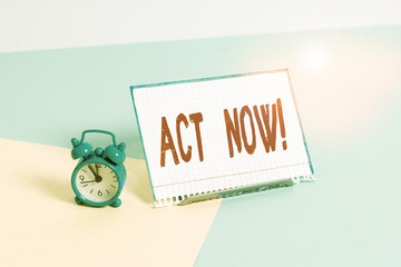 Word writing text Act Now. Business photo showcasing do not hesitate and start working or doing stuff right away Mini size alarm clock beside a Paper sheet placed tilted on pastel backdrop