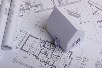 White family paper house, house projects plan and blueprints in the background. Minimalistic and simple concept, style. Horizontal orientation.