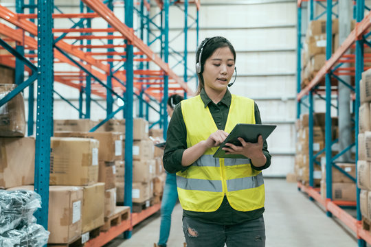 Businesswoman using digital tablet in distribution warehouse. young woman staff in headset talking to customer online while walking in large storehouse. female colleague in background check inventory