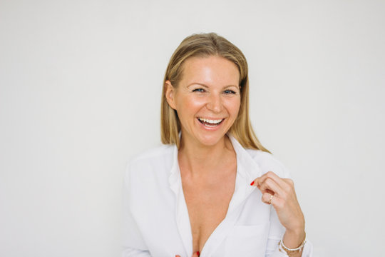 Portrait of happy blonde forty year woman with long hair in white shirt on white wall background isolated
