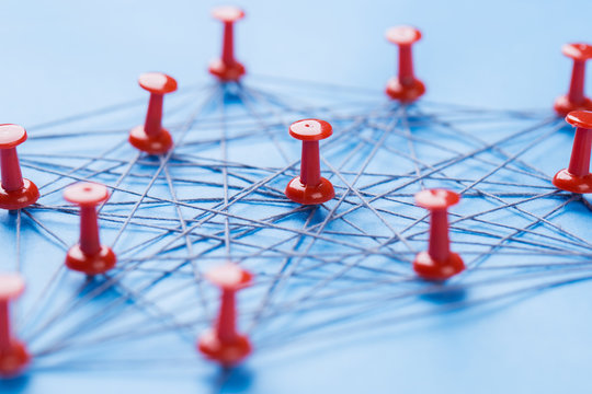 network with red pins and string, An arrangement of colorful pins linked together with string on a blue background suggesting a network of connections.