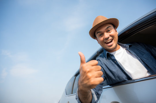 Asian men wear hats The blue shirt is driving and thumbs up This picture is about Travel by car, car insurance, and buying and selling cars
