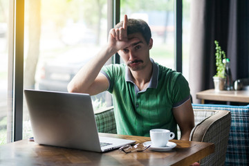 I am loser. Young sad businessman in green t-shirt sitting and looking at camera with loser gesture on his forehead and feel sad. business and freelancing concept. indoor shot near window at daytime